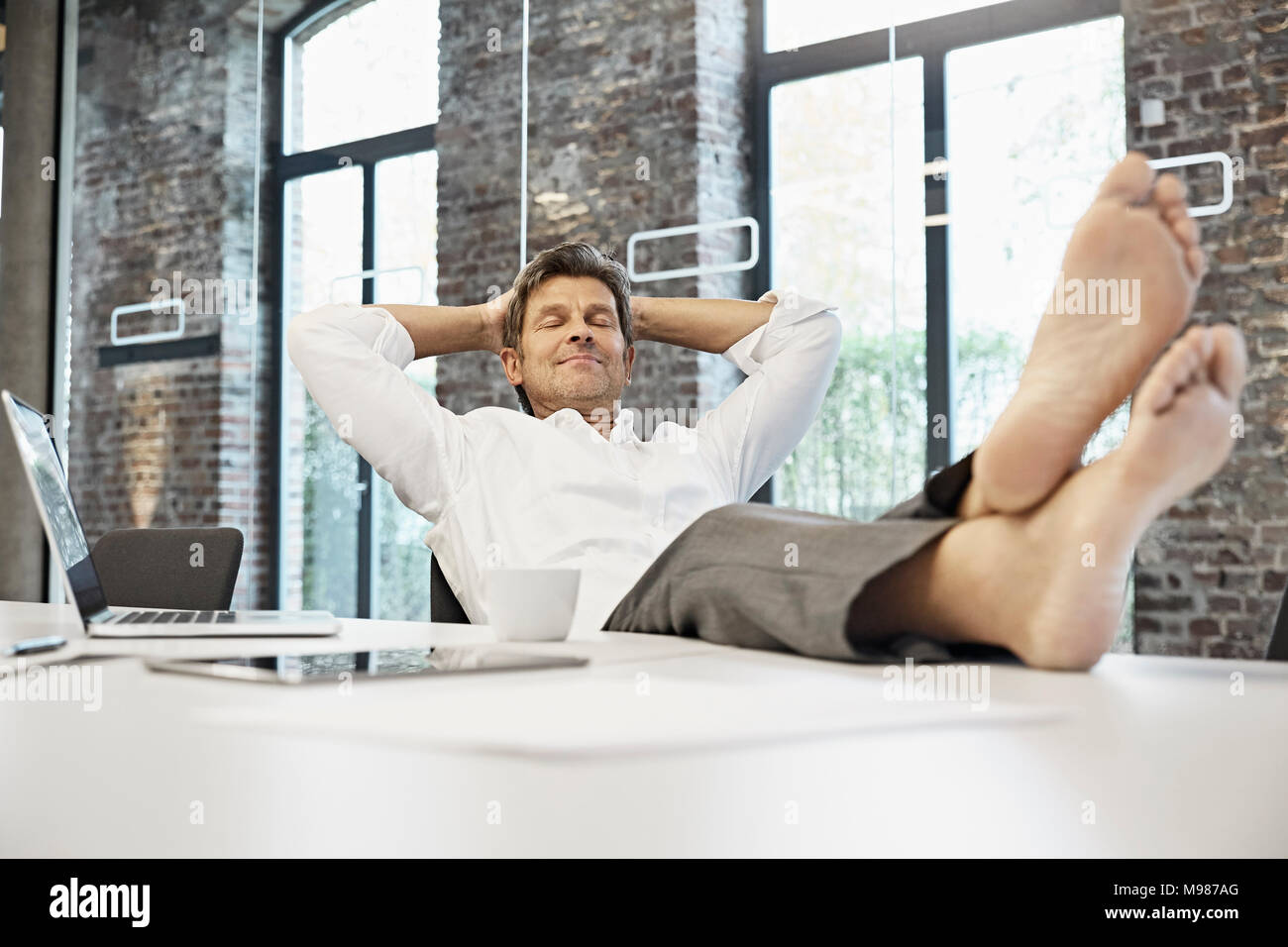 Barefooted businessman relaxing in conference room of modern office - Stock Image