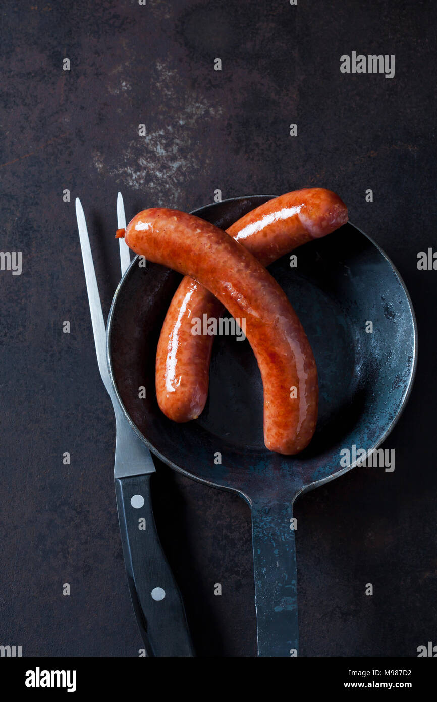 Two minced pork sausage in pan and a meat fork on rusty metal - Stock Image