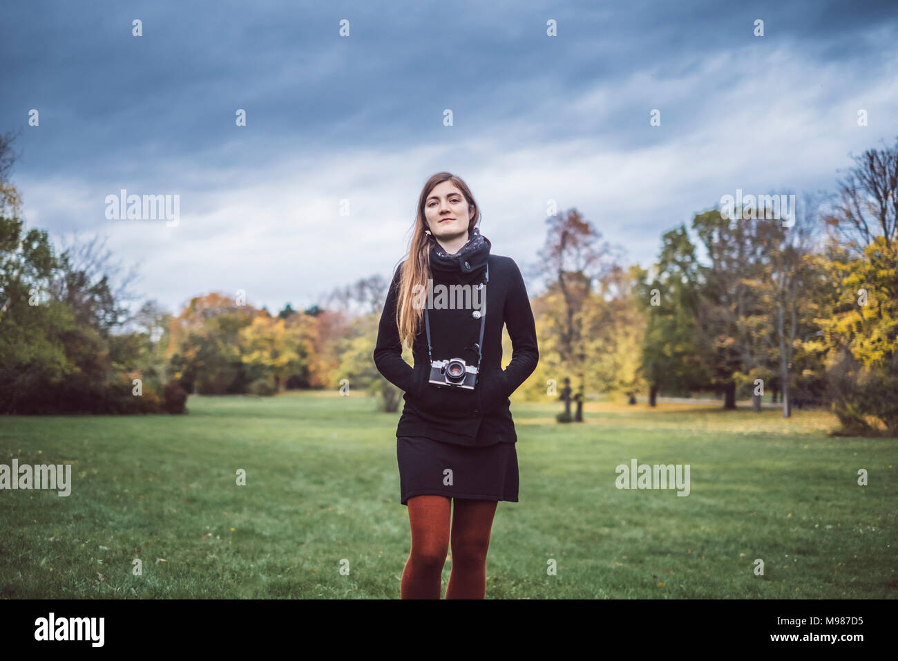Portrait of young woman with camera walking on a meadow in autumnal park Stock Photo
