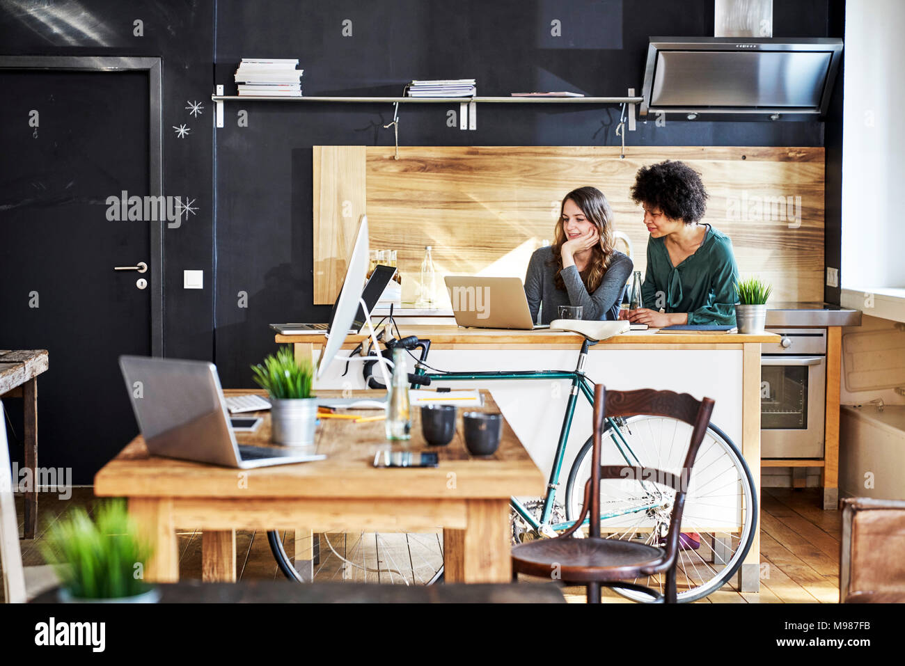 Two young women using laptop in modern office - Stock Image