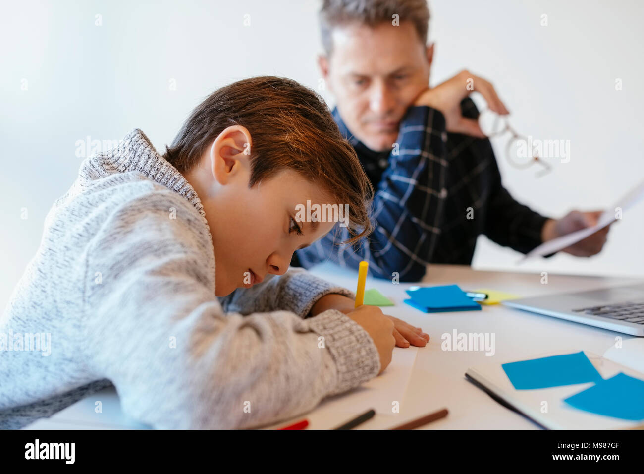 Businessman at desk in office looking at son drawing - Stock Image