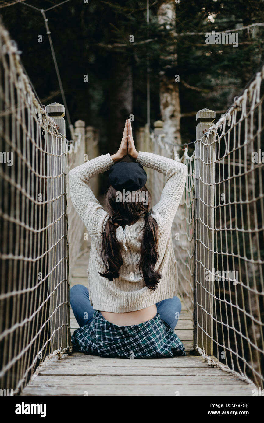 Young woman in yoga pose sitting on a suspension bridge - Stock Image
