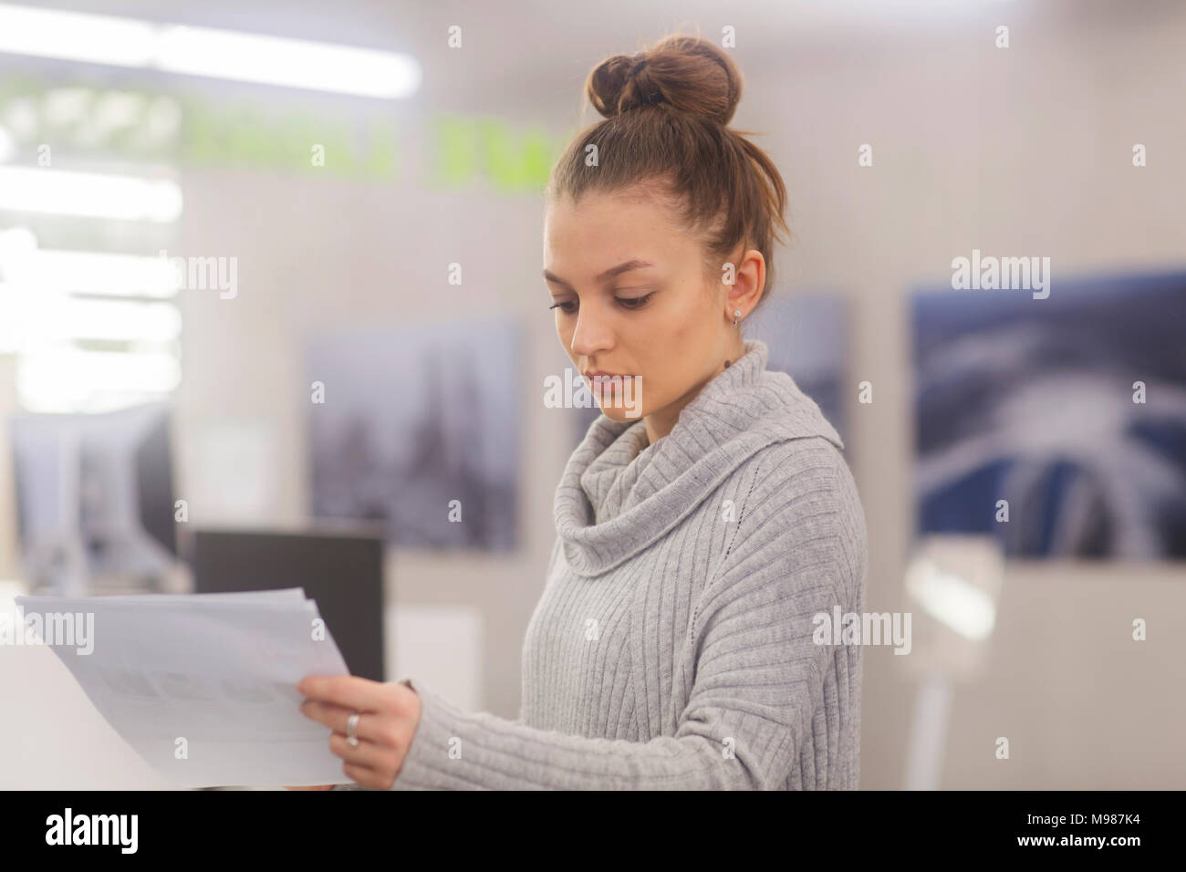 Portrait of young woman at work in an office - Stock Image