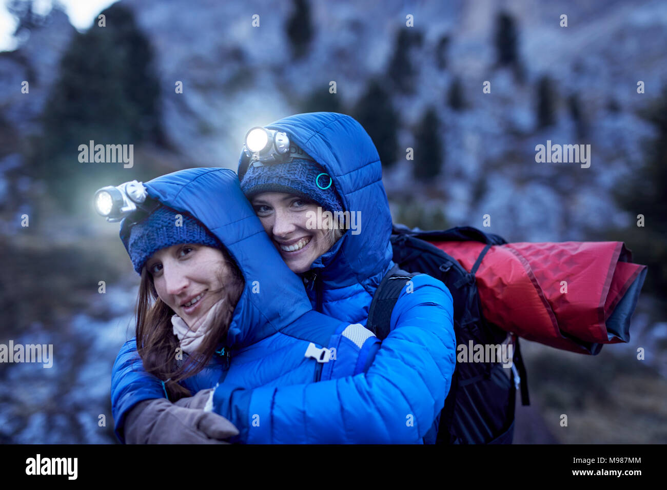 Two happy young women wearing headlamps embracing in the mountains - Stock Image