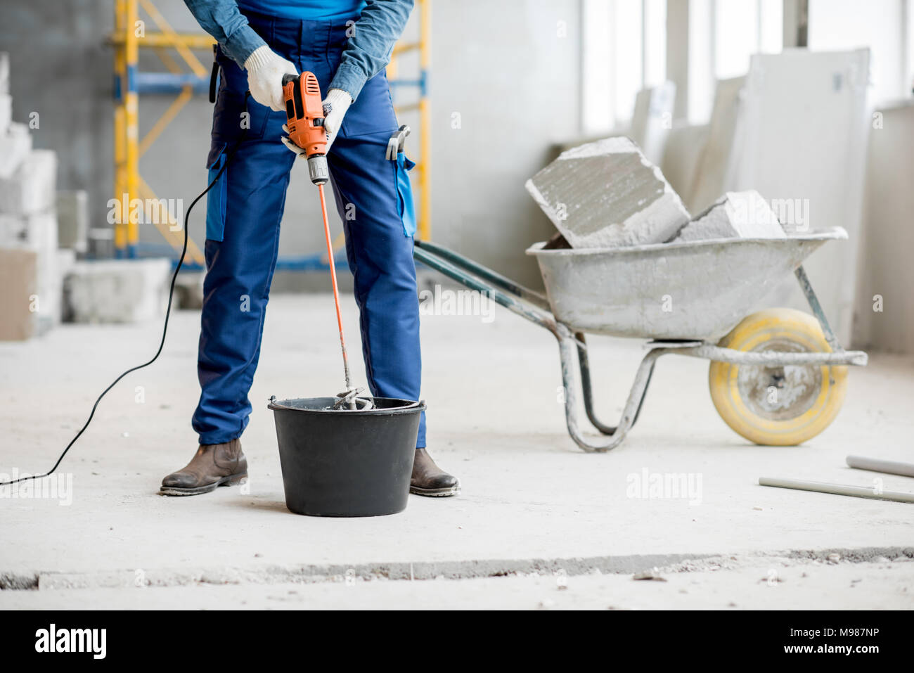 Builder mixing plaster at the construction site Stock Photo