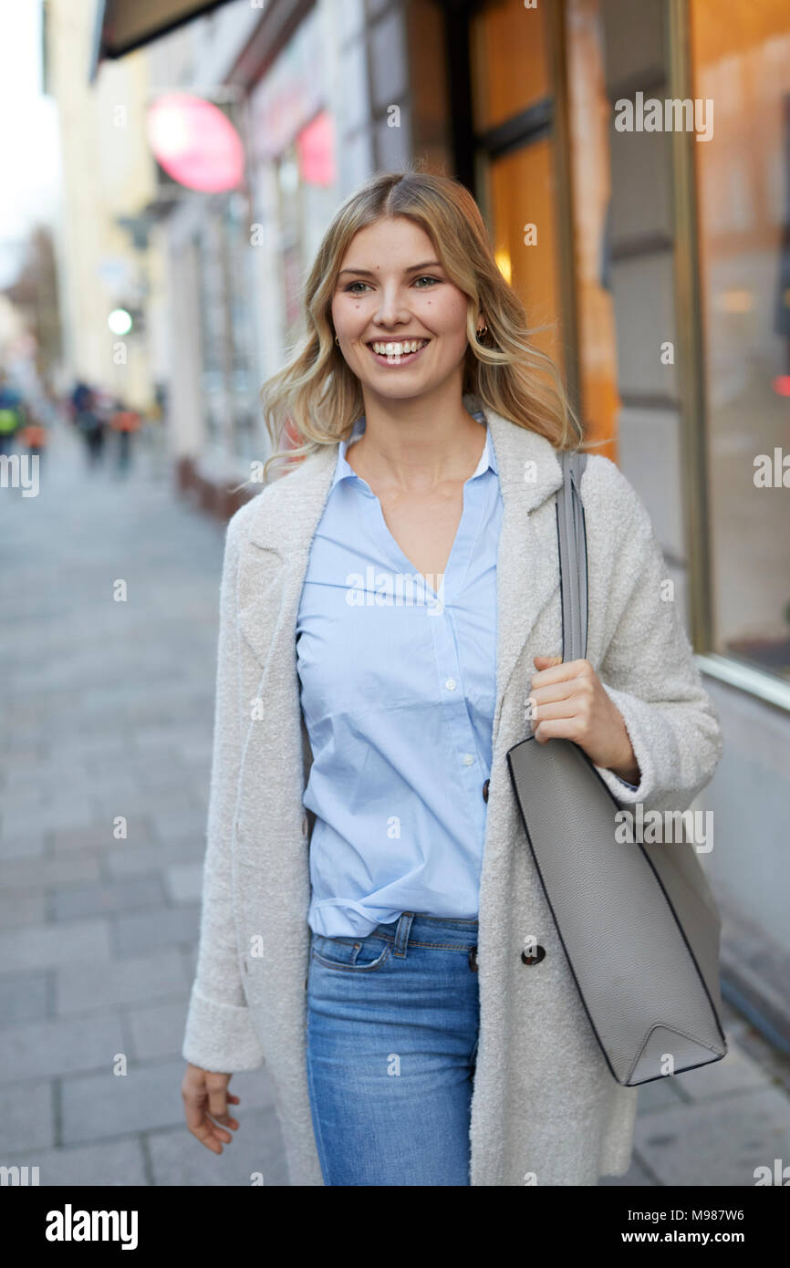 Portrait of smiling woman walking in the city - Stock Image
