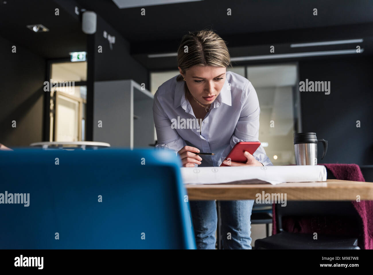 Young woman with cell phone and plan at table in office - Stock Image