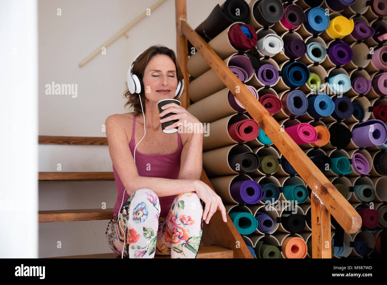 Relaxed mature woman listening to music next to assortment of yoga mats - Stock Image