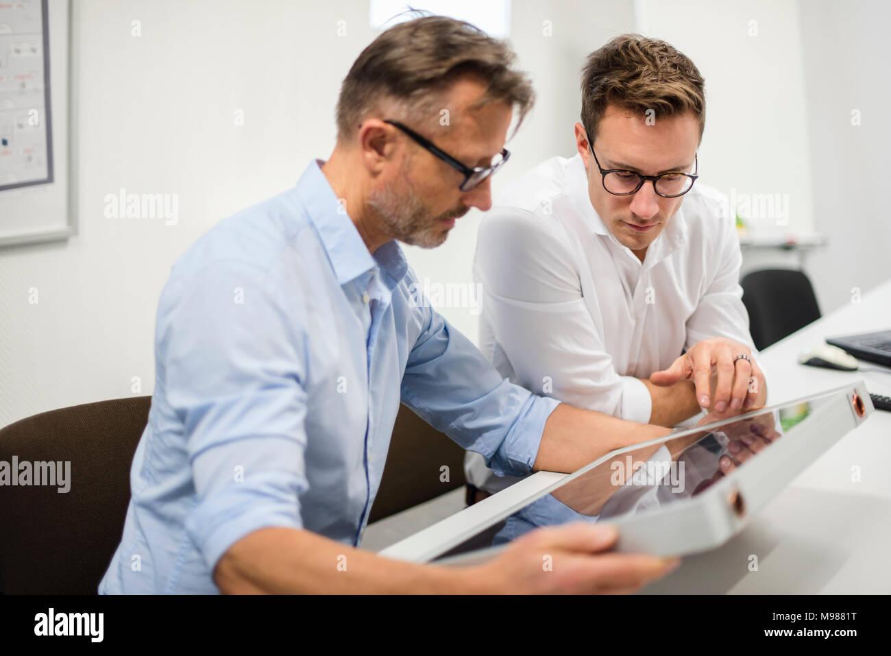 Two businessmen examining solar panel on desk in office - Stock Image