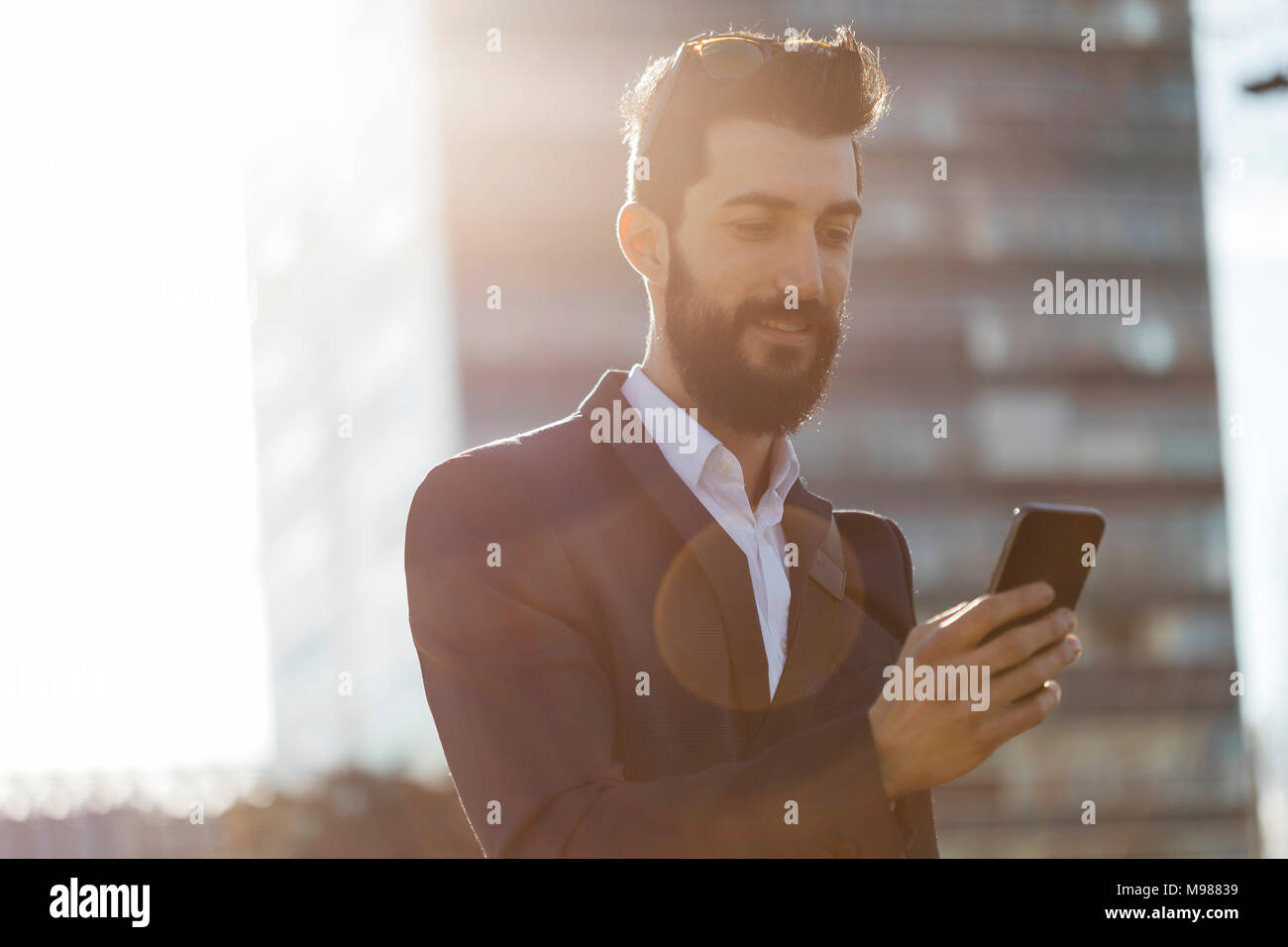 Businessman using cell phone outside office building - Stock Image