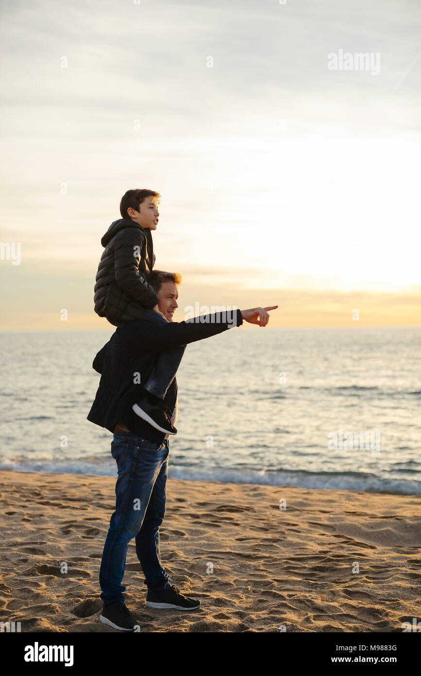 Father carrying son piggyback on the beach at sunset pointing finger - Stock Image