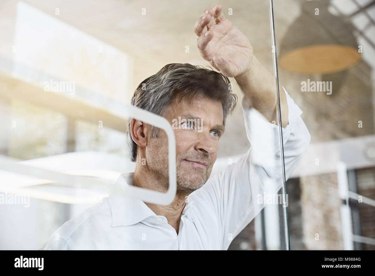 Portrait of mature businessman leaning against glass wall in office - Stock Image