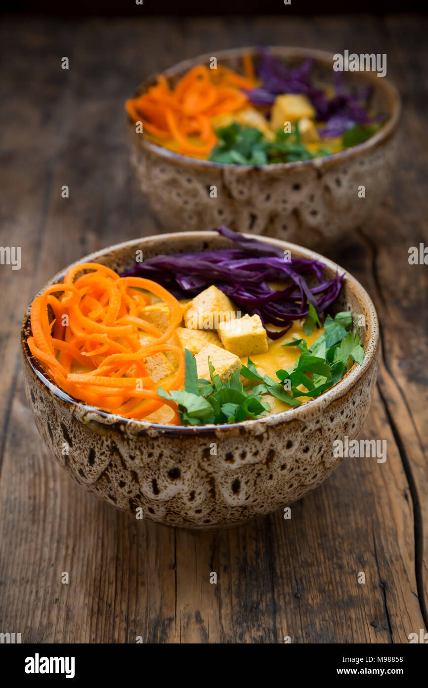 Turmeric curry dish with carrot, tofu, red cabbage and parsley in bowl - Stock Image