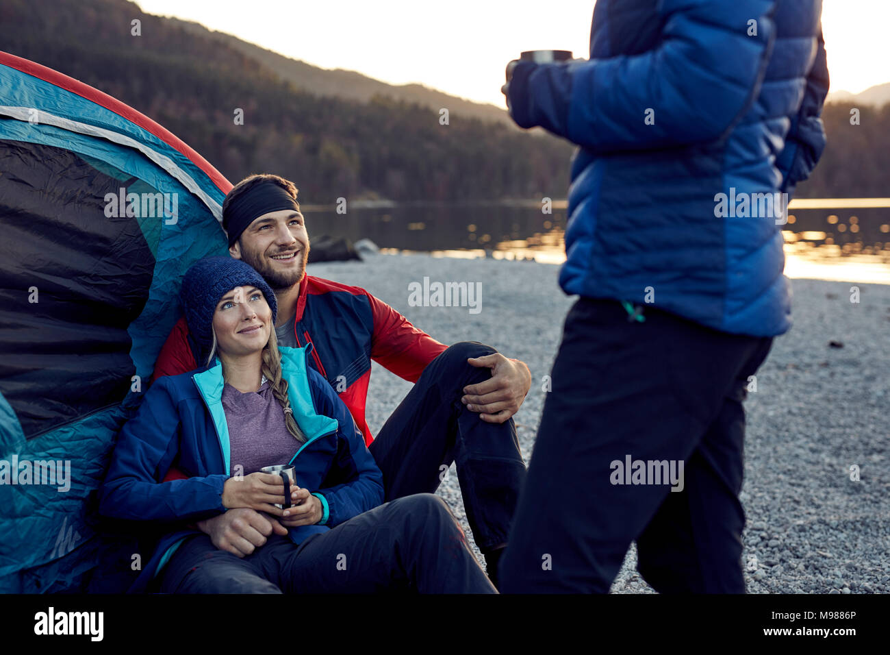 Smiling young couple with friend sitting at tent at lakeshore - Stock Image