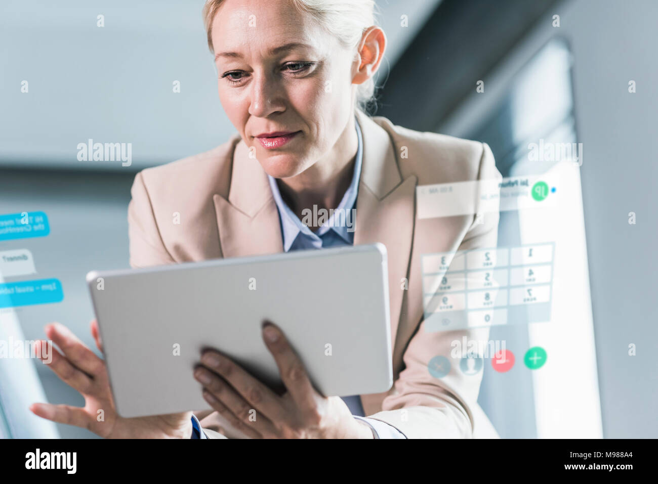 Businesswoman sitting in office, using digital tablet Stock Photo