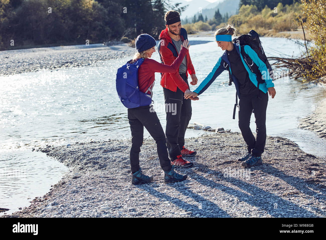 Group of friends hiking shaking hands at the riverside - Stock Image