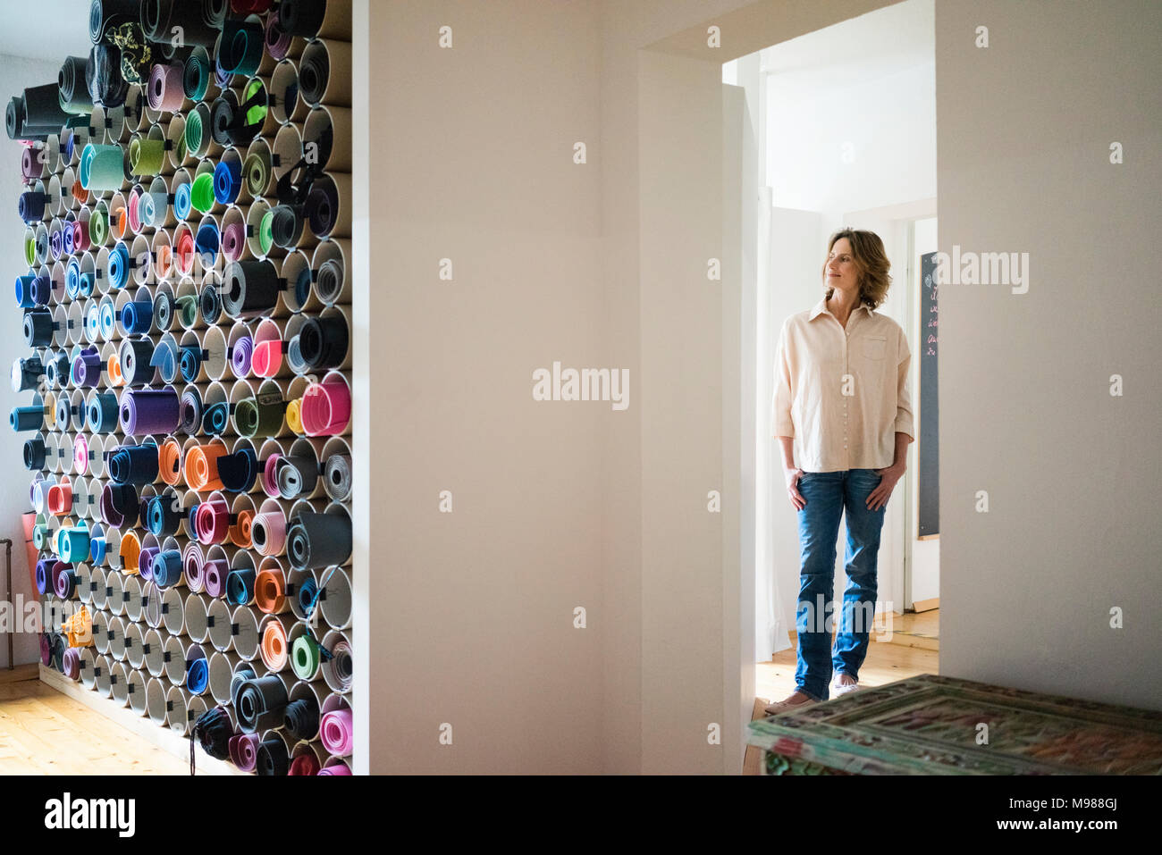 Mature woman standing in a room with assortment of yoga mats Stock Photo