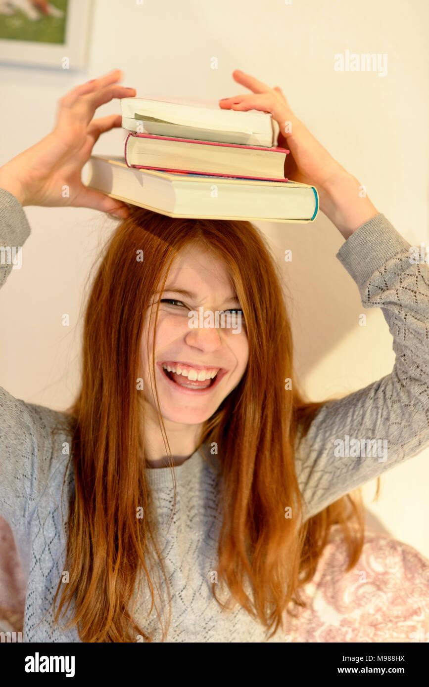Mädchen mit Büchern auf dem Kopf, Buchstapel, Leseratte, Bayern, Deutschlaned - Stock Image