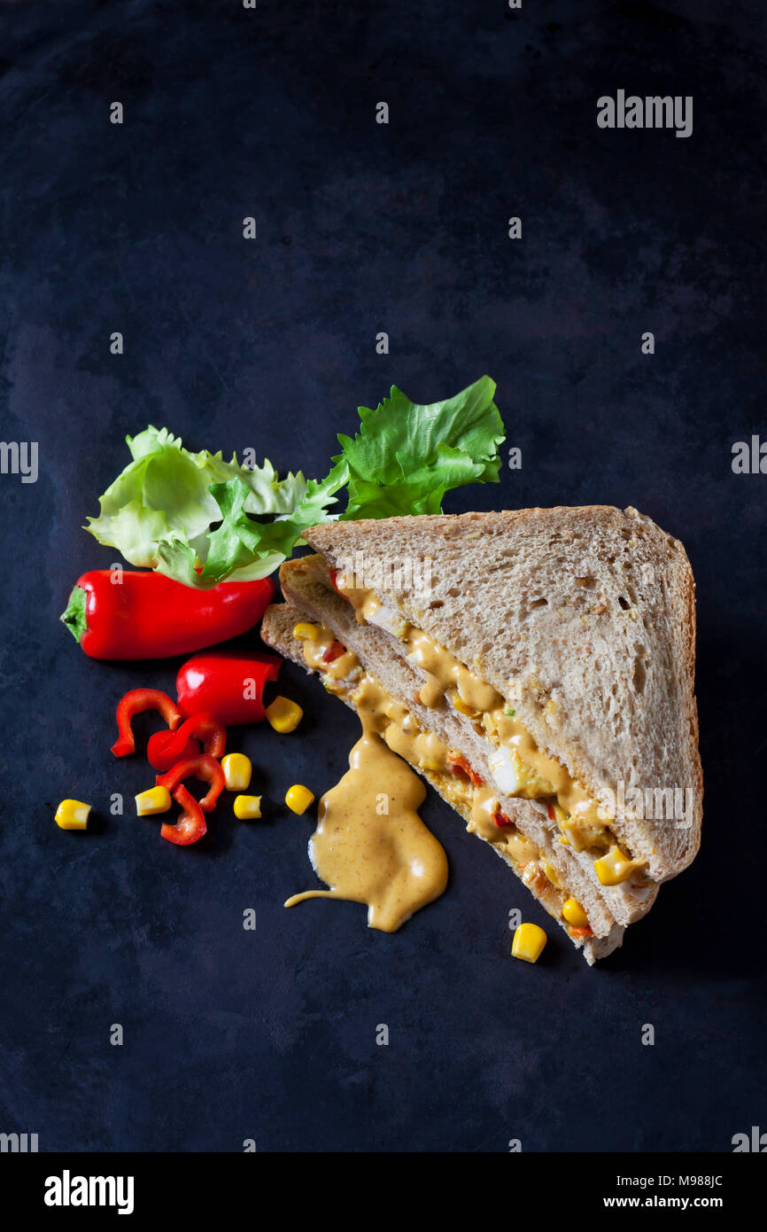 Chicken sandwich with corn, pepperoni and curry sauce on dark ground - Stock Image