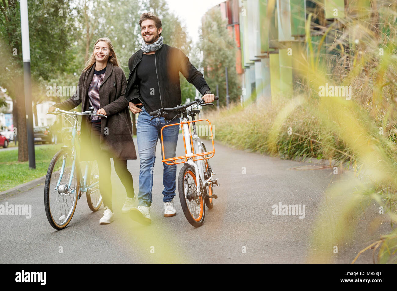 Smiling couple walking with bicycles on a lane - Stock Image
