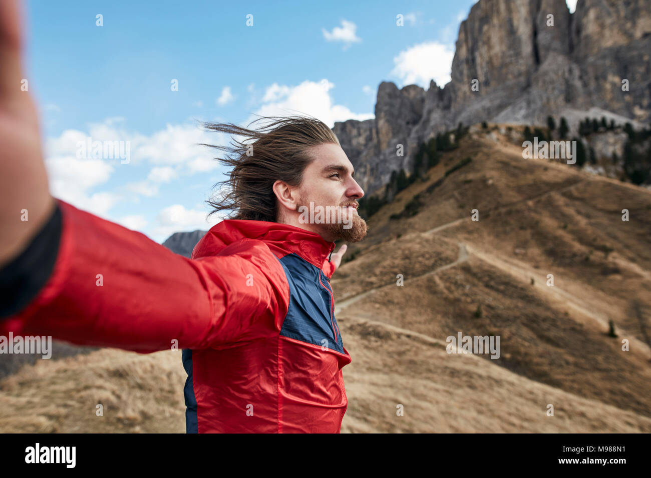 Young man leaning against the wind in the mountains - Stock Image