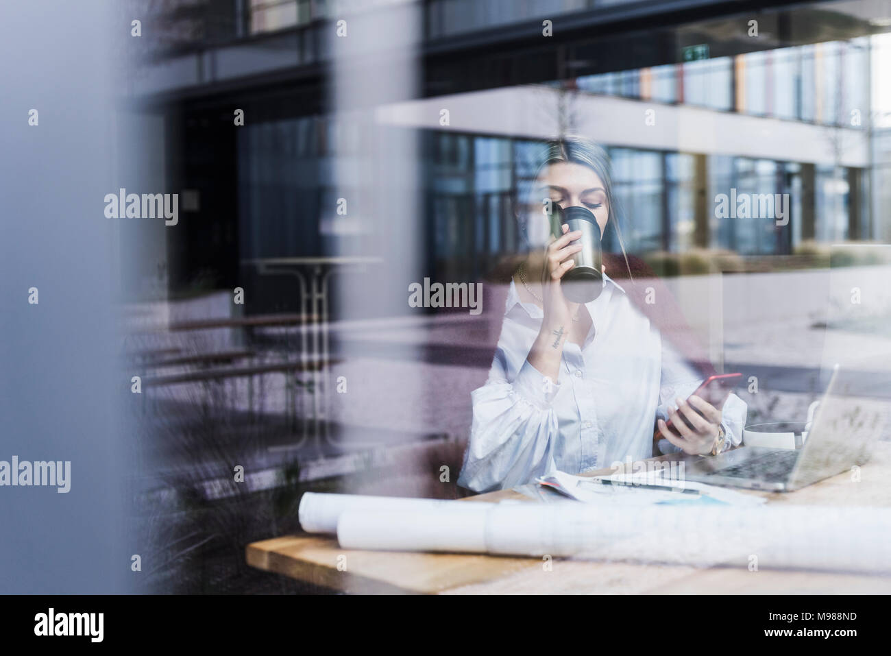 Young woman with laptop, cell phone and documents drinking coffee behind windowpane - Stock Image