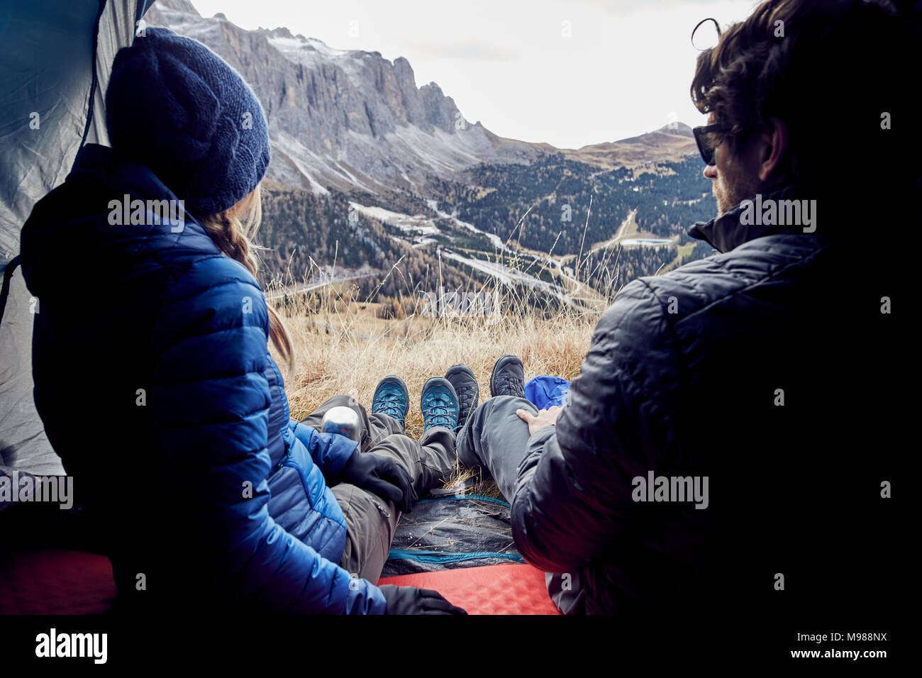 Couple sitting in tent in the mountains looking at view - Stock Image