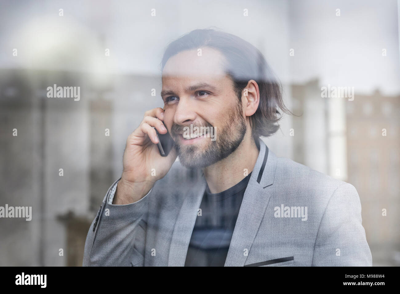 Portrait of smiling businessman on the phone behind windowpane - Stock Image