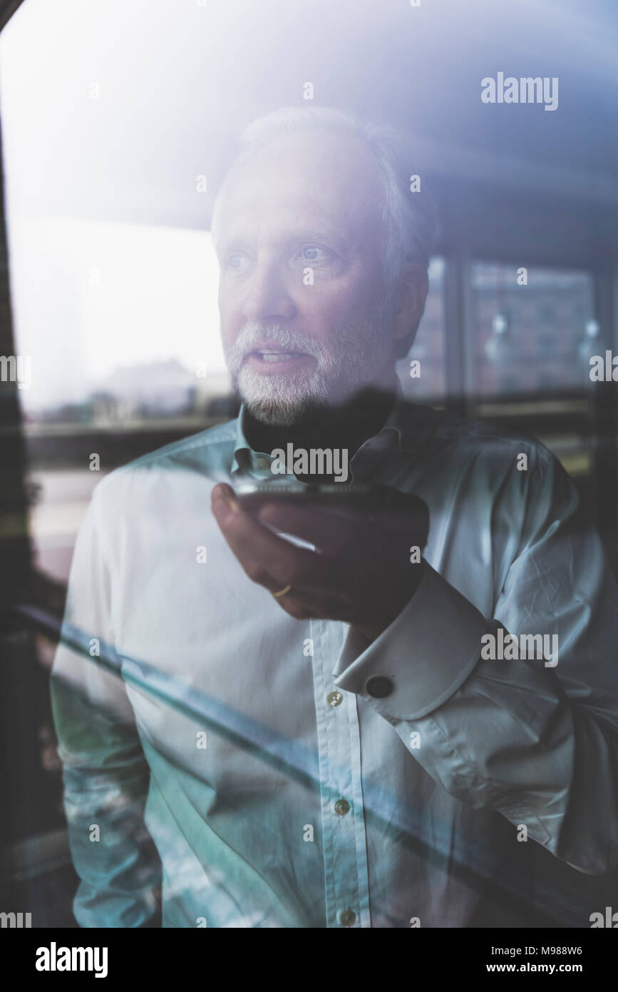 Portrait of mature businessman at the window using cell phone - Stock Image