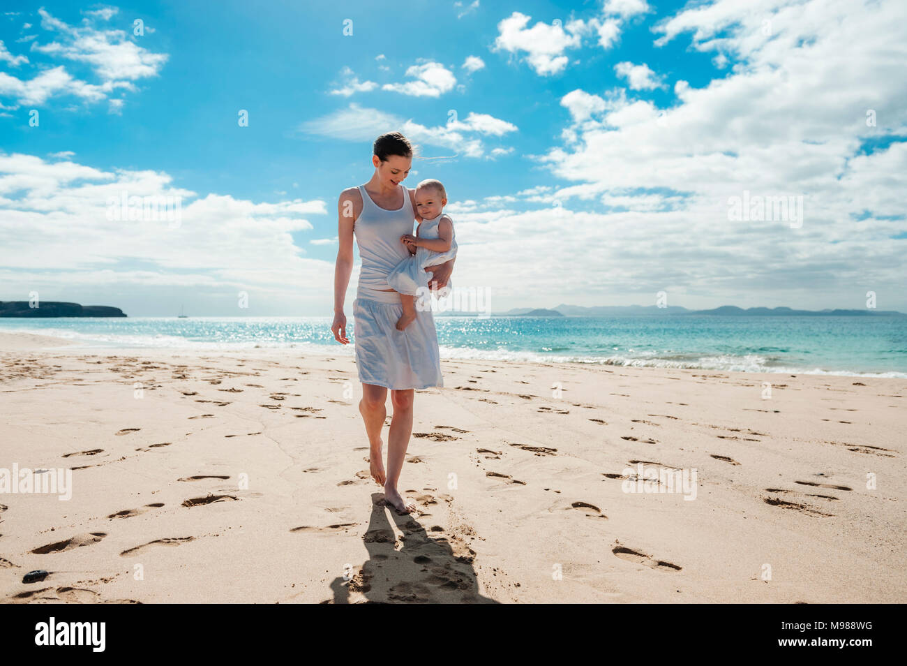 Mother walking with little daughter on the beach - Stock Image