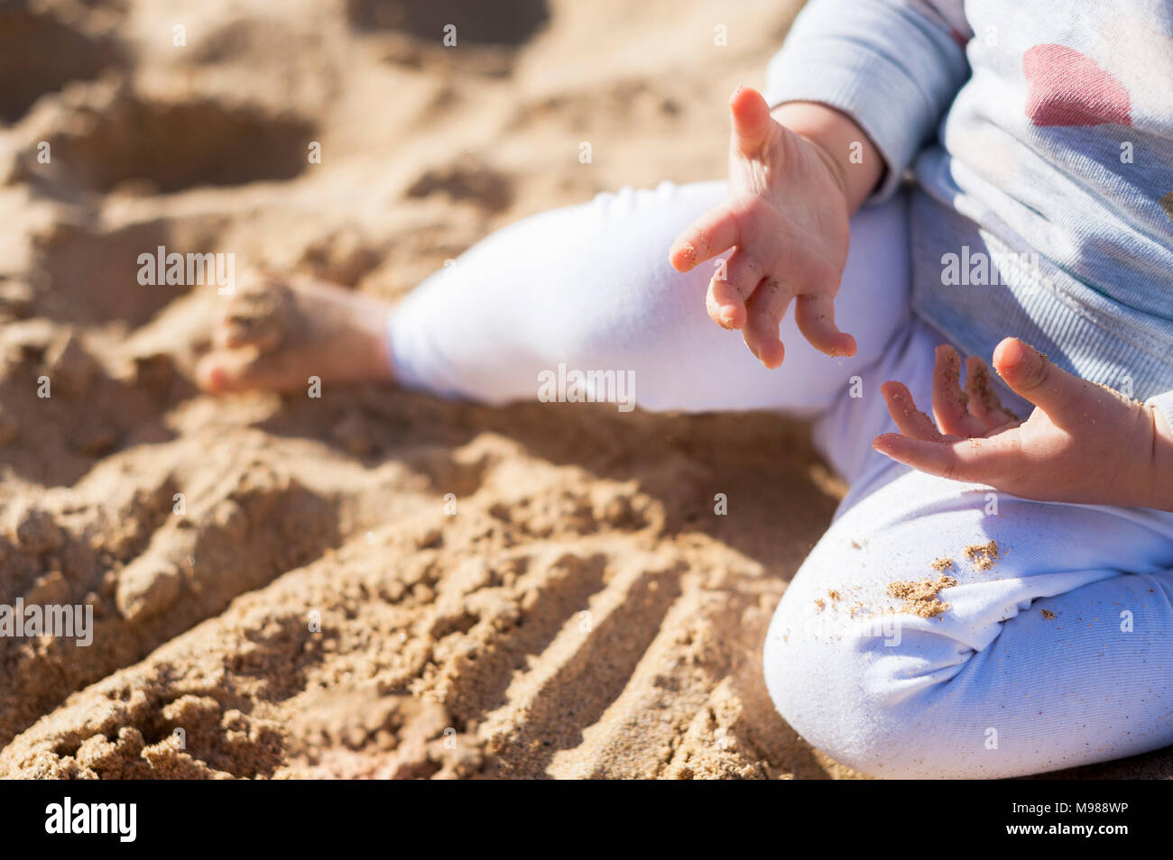 Baby girl's hand with sand - Stock Image