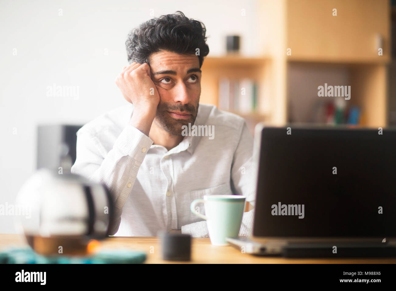 Portrait of thinking businessman at desk in his office - Stock Image