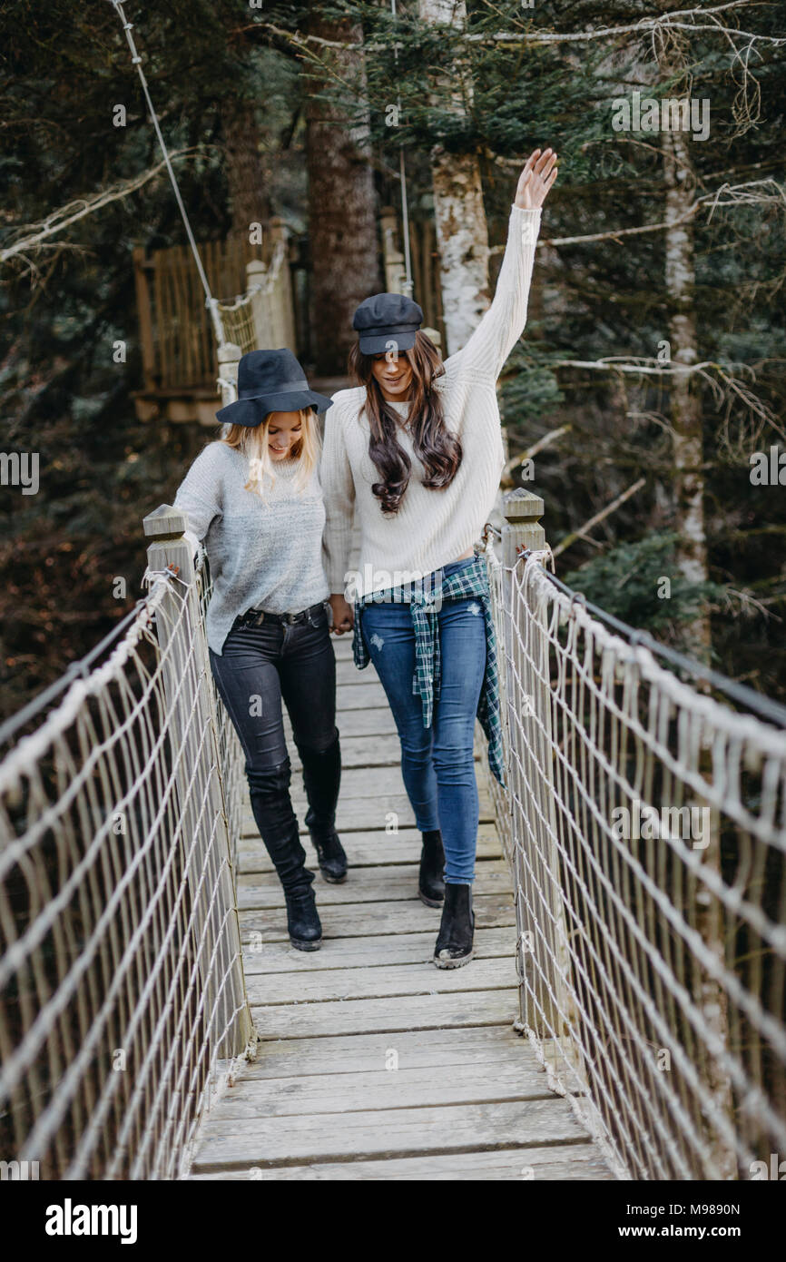 Two happy young women walking on a suspension together - Stock Image