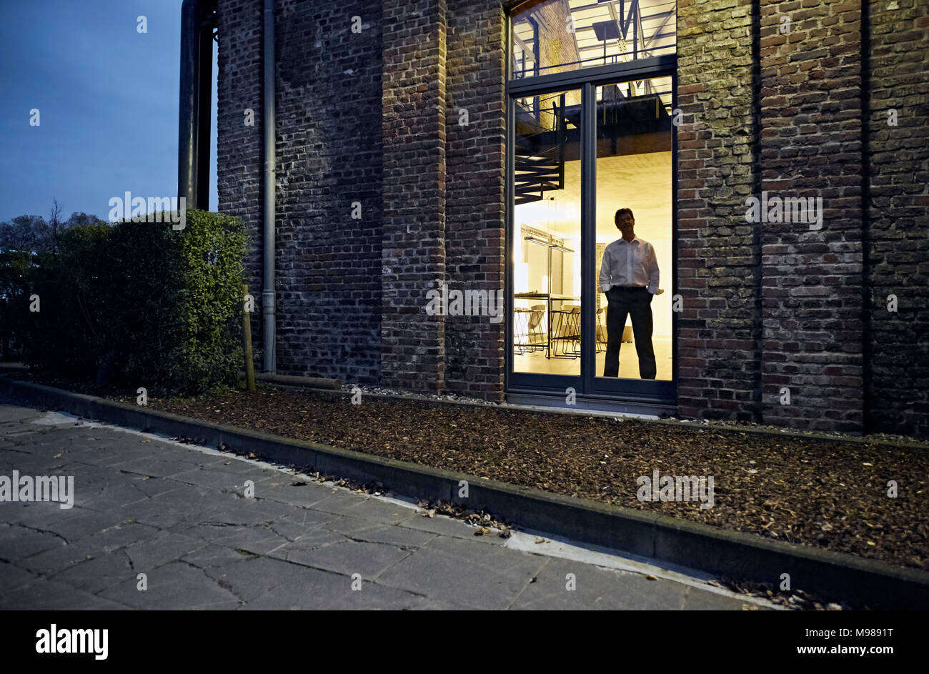 Exterior view of man standing at window of modern building at night - Stock Image