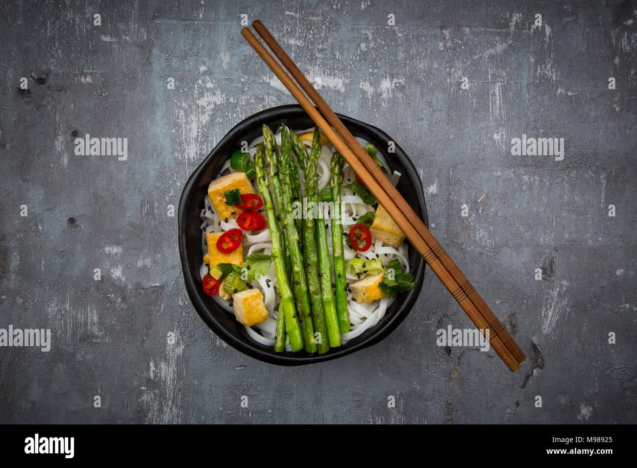 Bowl of vegan Pad Thai with mini green asparagus and tofu, chili, spring onion, peanut and coriander - Stock Image