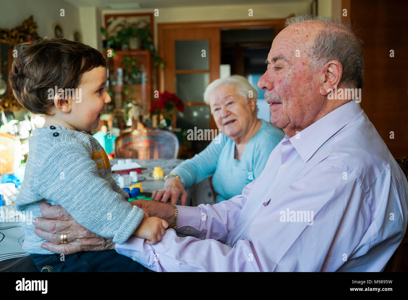 Great-grandparents playing with baby girl at home - Stock Image