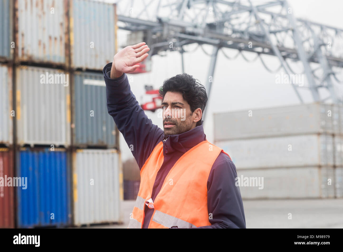 Man wearing reflective vest working at container port - Stock Image