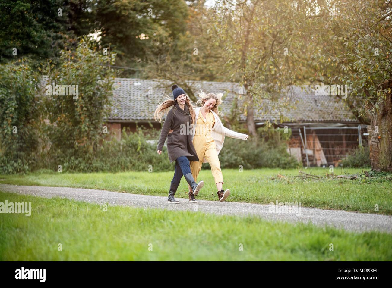 Two happy women walking in rural landscape - Stock Image