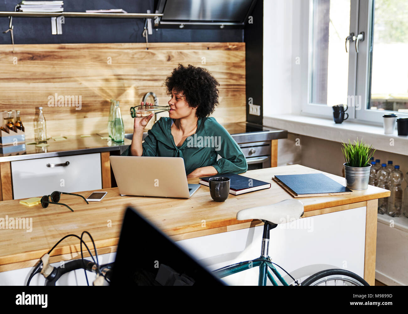 Young woman using laptop on kitchen counter - Stock Image