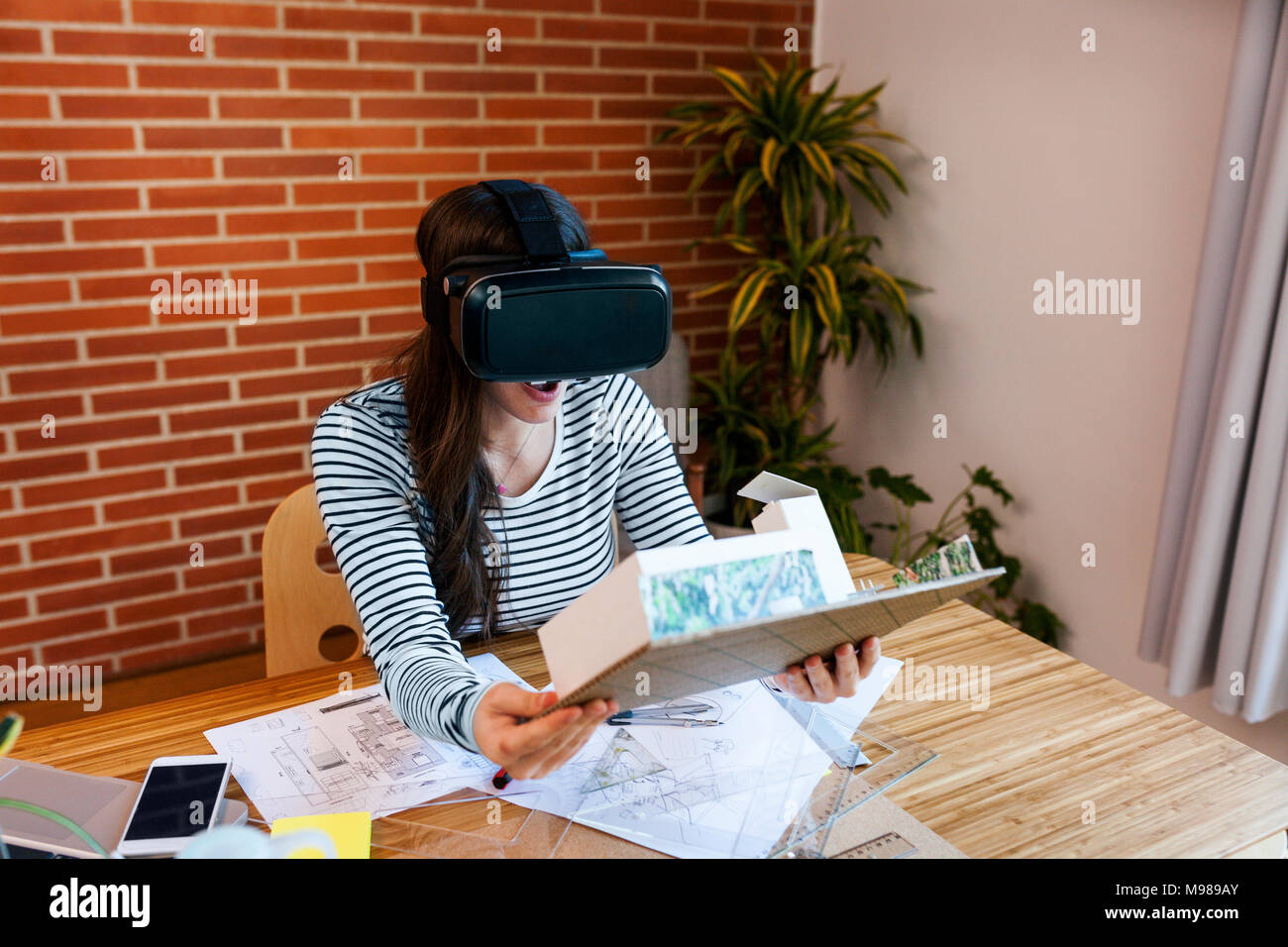 Young woman working in architecture office, looking at model with VR goggles - Stock Image