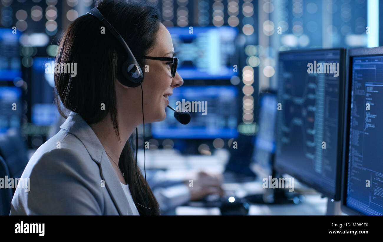 In the System Control Center Woman working in a Technical Support Team Gives Instructions with the Help of the Headsets. Possible Air Traffic - Stock Image