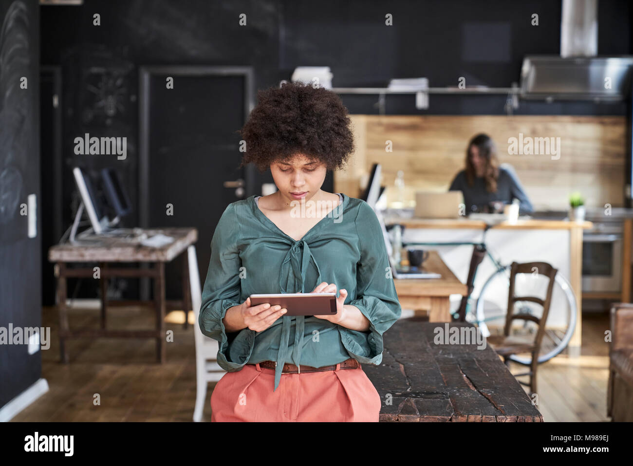 Young woman using tablet in modern office - Stock Image