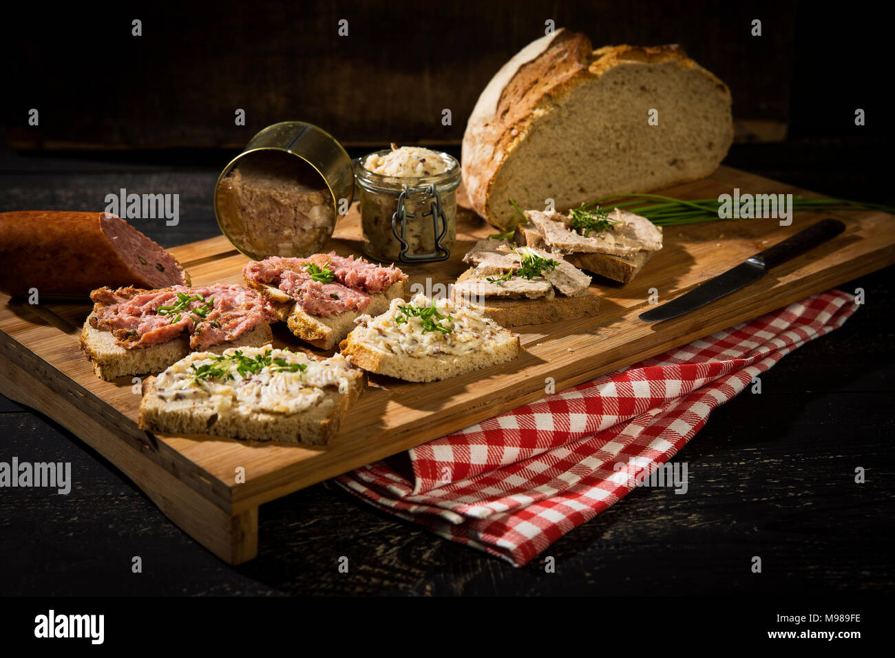 Crusty bread, crackling fat, liver sausage, minced and pork sausage - Stock Image