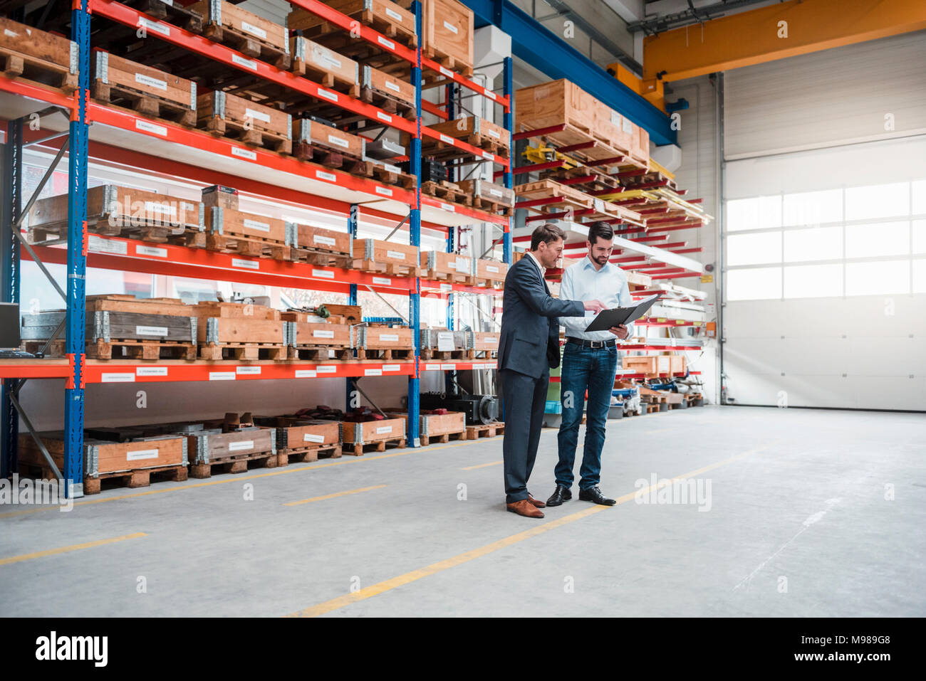 Two men walking and talking in factory shop floor - Stock Image