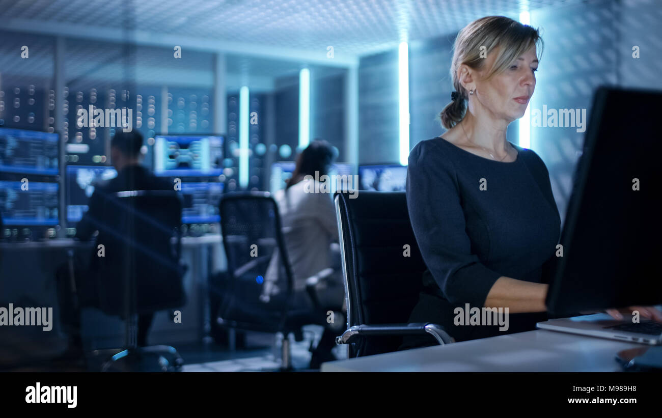 Female IT Engineer Works on Her Desktop Computer in Government Surveillance Agency. In the Background People at Their Workstations with Screens Stock Photo