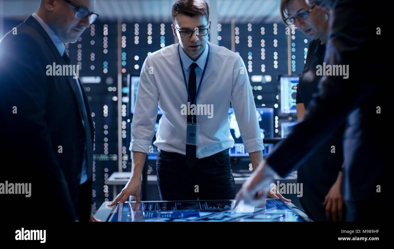 Three Government Agents Working at the Big Table in Monitoring Room. Room is Full of State of the Art Technology. Computers with Animated Screens. - Stock Image