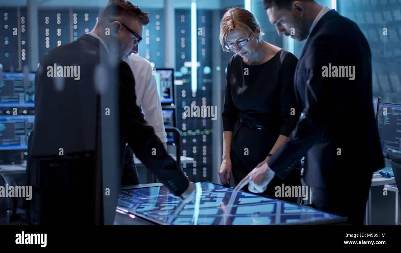 Government Agents Working at the Big Table in Monitoring Room. Room is Full of State of the Art Technology. Computers with Animated Screens. - Stock Image