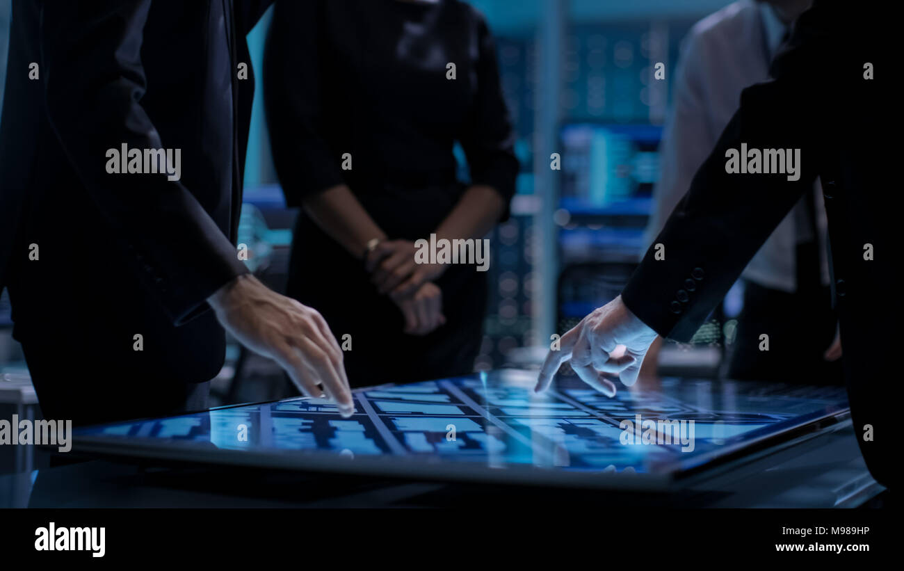 Corporate Managers Working at the Table in Monitoring Room. Room is Full of State of the Art Technology. Computers with Animated Screens. - Stock Image