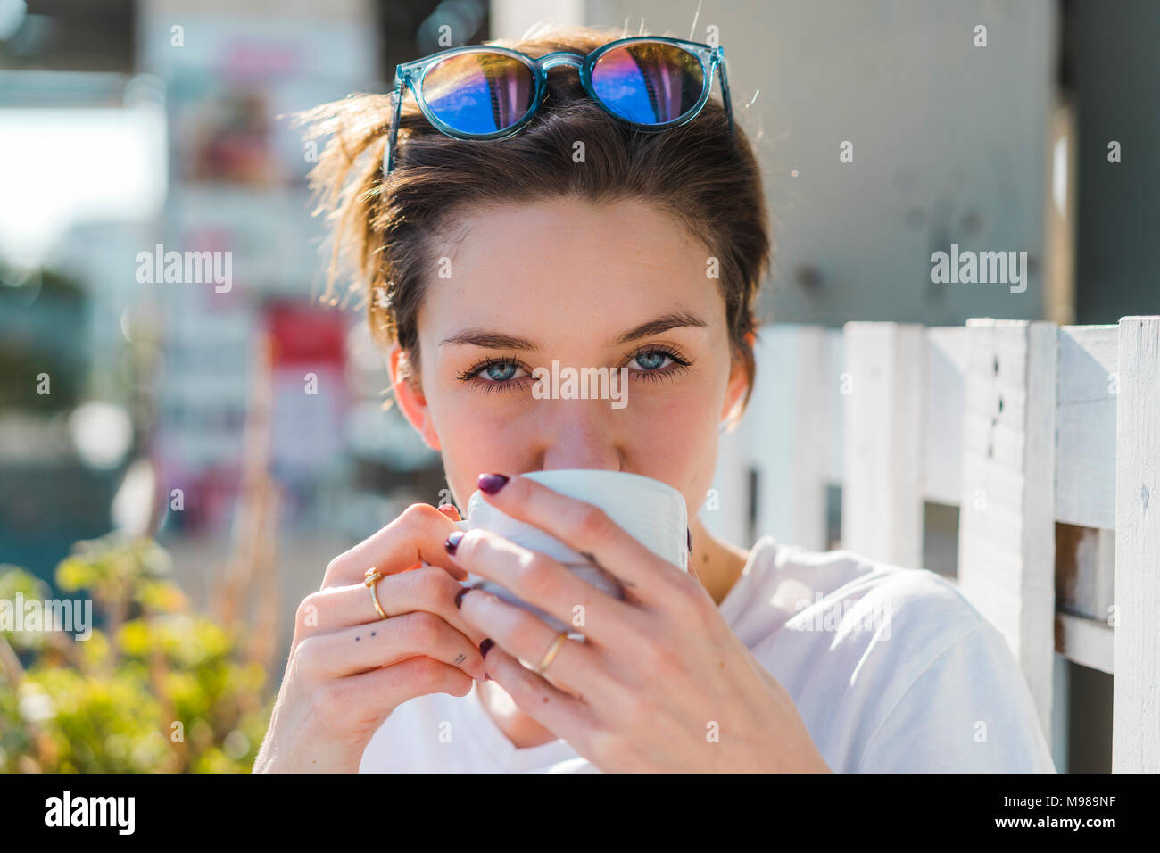 Portrait of woman drinking cup of coffee - Stock Image