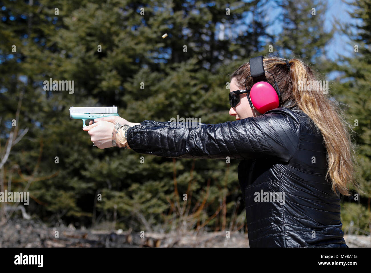 Woman shooting a handgun and the ejected shell is in the air. - Stock Image